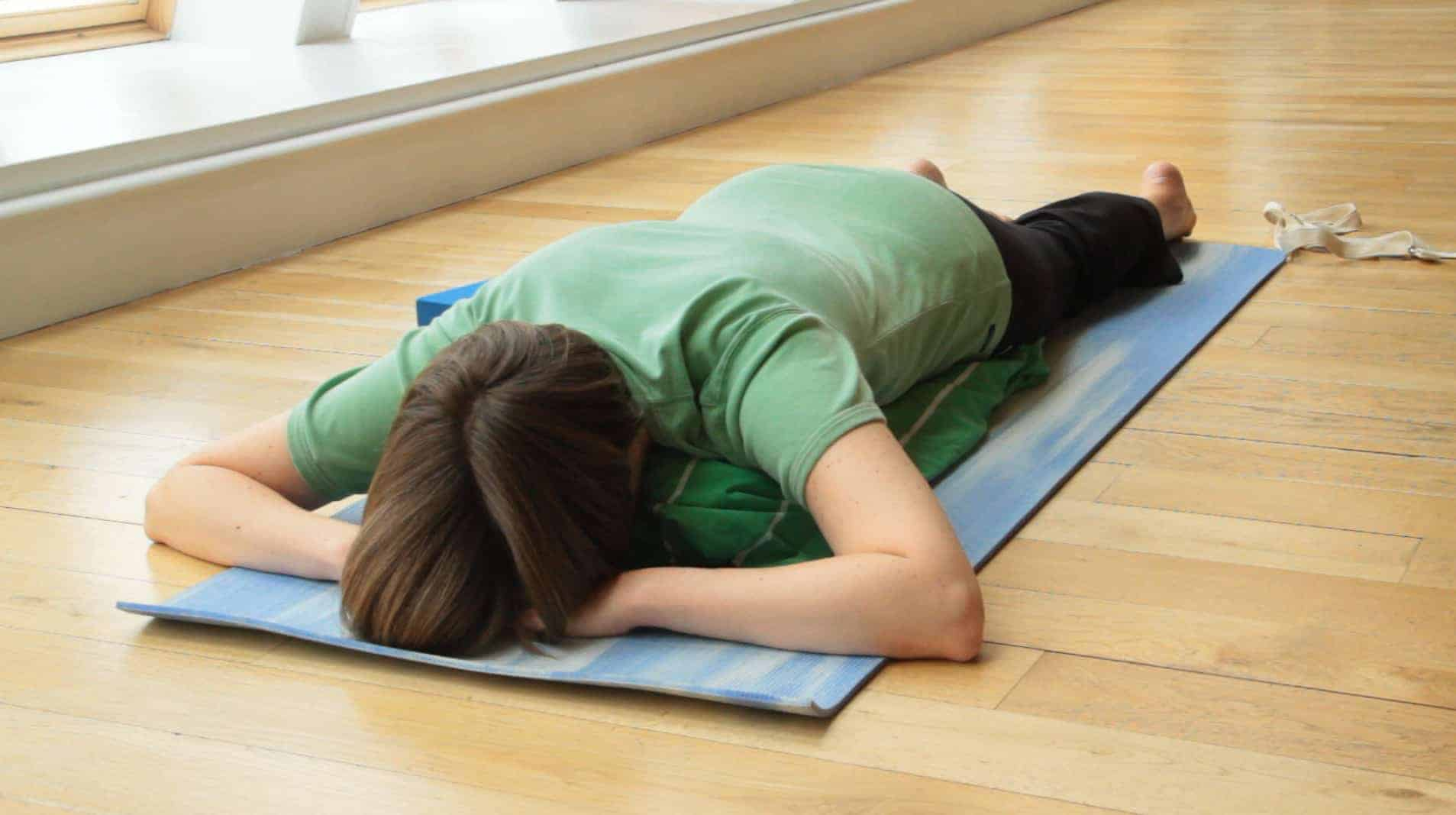 Lying prone with pillow crosswise under abdomen useful for disc